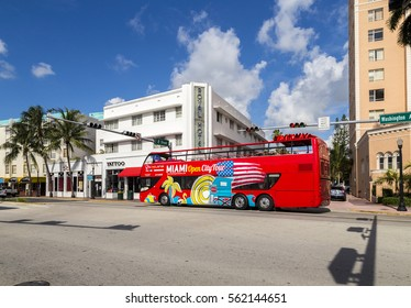 MIAMI, USA - AUG 5, 2013: Hop on Hop off tourist bus at washington Avenue with art deco hotel Royal. The art deco district at south beach is famous for its buildings from the thirties of last century.