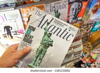 MIAMI, USA - AUGUST 22, 2018: The Atlantic magazine in a hand over a stack of magazines. The Atlantic is a popular American magazine and multi-platform publisher.