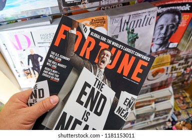 MIAMI, USA - AUGUST 22, 2018: Fortune magazine in a hand over a stack of magazines. Fortune is a popular American multinational business magazine headquartered in New York City