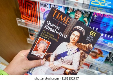 MIAMI, USA - AUGUST 23, 2018: Time magazine with Queen Elizabeth II on the cover in a hand. Time is an American weekly news magazine