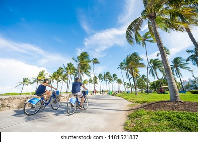 MIAMI, USA - CIRCA JUNE 2017: Tourists ride  'Citi Bikes' bicycle shares along the Miami Beach promenade with backdrop of iconic art-deco buildings and palm trees of Lummus Park on Ocean Drive.