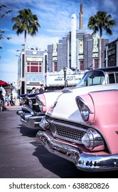 Miami, USA – JULY 15 2014: A row of pink vintage cars parked in front of a hotel and palm trees.
