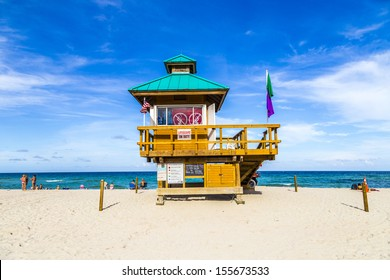 MIAMI, USA - JULY 29: people relax at Sunny Isles beach protected by guards in lifeguards huts on July 29, 2013 in Miami, USA. In 1920, Harvey Baker Graves purchased the  land  as a tourist resort.