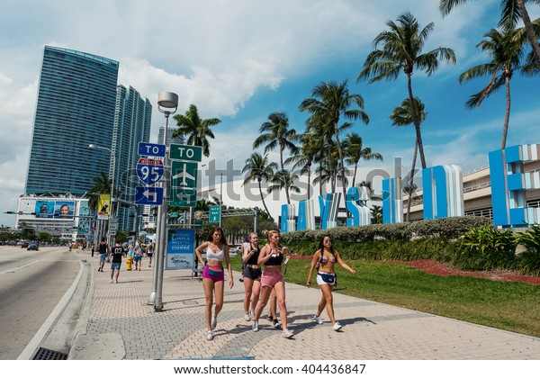 MIAMI, USA - MARCH 18, 2016: Young women walking on the street going to Ultra Music Festival in front of Bayside sign.