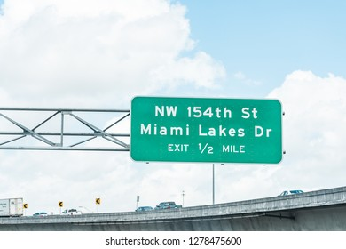 Miami, USA - May 2, 2018: Road street highway green signs in Florida with text for exit to NW Northwest 154th street st Miami Lakes Dr Drive in half a mile