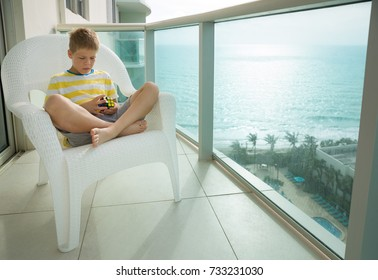 Miami, USA, October 3 2017: Rubik's cube in child's hands. Boy holding Rubik's cube and playing with it while sitting on a balcony of high building with ocean view on a sunny day.