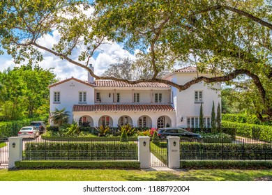 Miami, USA-July 7, 2018: Luxurious Coral Gables houses. Facade of a white two storey house with slanted roofs and well maintained front lawn. The area is a tourist attraction in the city