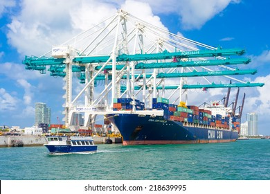 MIAMI,USA - AUGUST 26, 2014 : Ship with containers unloading cargo at the Port of Miami assited by big modern cranes