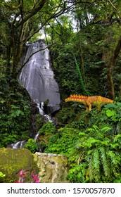 Miaoli, Taiwan - APR 13, 2019: Model dinosaur decoration next to the small waterfall view in Sud Vista.