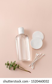 Micellar cleansing water, cotton buds and discs to remove cosmetics and cleanse the skin on pink. Copy space text