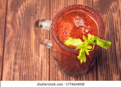Michelada beer with tomato juice. Clamato with beer on wooden table. Mexican drink.