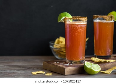 Michelada (Mexican Bloody Beer) with Spisy Rim and Tomato Juice served with Limes and Nacho Chips. Summer Alcohol Cocktail Michelada.