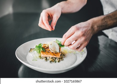 Michelin chef preparing fish food on dark table, hands of cook