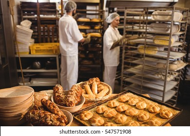 Michetta and sweet food on a table while male and female baker working in background at bakery shop
