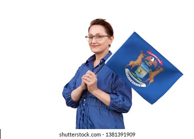 Michigan flag. Woman holding Michigan state flag. Nice portrait of middle aged lady 40 50 years old holding a large state flag isolated on white background.