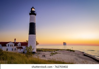 Michigan Lighthouse Coastal Sunset Background. Illuminated beacon of the Big Sable Lighthouse on the sandy coast of Lake Michigan at sunset. Ludington State Park in Ludington, Michigan.