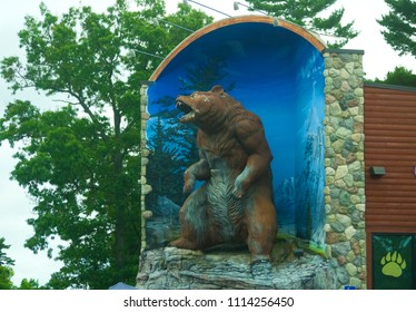 Michigan, United States - July 17, 2017: A large statue of a grizzly bear stands above Traverse City Bear Company, a local retail store that sells souvenirs.