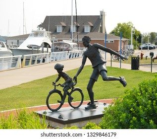 Michigan, USA, August 13, 2018: USA, Traverse city dad and son. Father teaches son to ride a bicycle