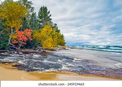 Michigan's Hurricane River flows across a sandy beach and into lake Superior in autumn at Pictured Rocks National Lakeshore.