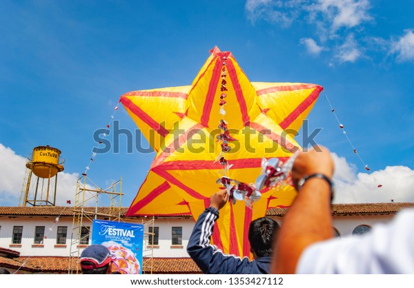Michoacan, MEXICO - july 22, 2012: Close up at the hand of a young man holding a hot air balloon by means of a tie decorated with colored plastic flowers
