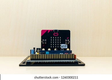 Micro bit is a small electronic device used to learn modern technology as a basis for programming in computer science and computing science. Concept code for kid. With copy space wooden background