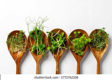 Micro greens in wooden spoon on white background