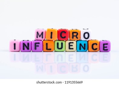 MICRO INFLUENCE word block concept on white reflection table