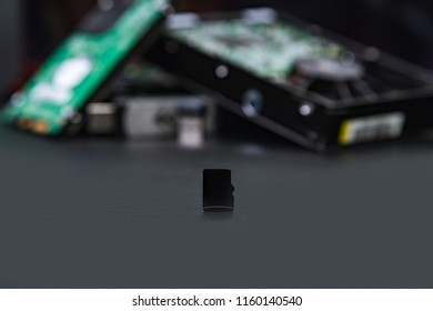 Micro SD cards on the background of hard drives as a replacement for old storage methods. Computer and hdd concept.