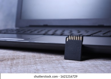 Micro SD memory card adapter on laptop background on the wooden table. close up front view