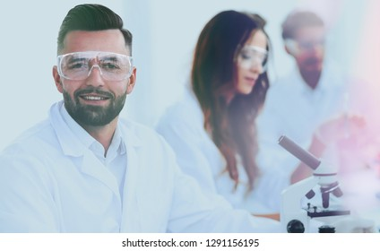 microbiologist and his colleagues are sitting in a modern labora