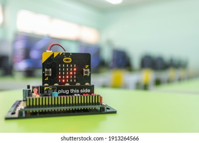 Microbit Educational microcontroller board showing a checkmark. With a backdrop of a computer room in the concept