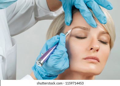 Microblading eyebrows. Cosmetologist making permanent makeup. Attractive woman getting facial care at beauty salon