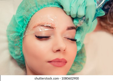 Microblading eyebrows work flow in a beauty salon. Woman having eye brows tinted eyes closed, hand in gloves holding tool and doing tattoo. Semi-permanent makeup for eyebrows. Focus on tinted eyebrow.