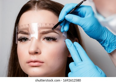Microblading eyebrows work flow in a beauty salon. Woman having her eye brows tinted. Semi-permanent makeup for eyebrows. Focus on model's face and eyebrow