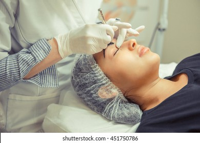 Microblading eyebrows work flow in a beauty salon. Woman having her eye brows tinted. Semi-permanent makeup for eyebrows.