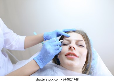 Microblading specialist, beautiful girl, makes imitation of eyebrows with sharp special needle on face of female client with light brown hair in blue cap that rests on white couch in modern day salon