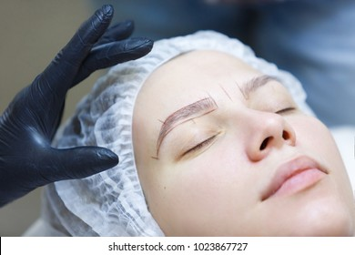 Microblading. Young girl doing the procedure of eyebrow coloring at the spa salon