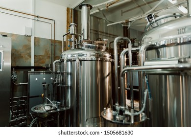 Microbrewery equipment. Close up tanks in brewery warehouse. Metal brewery vessels. Small business concept.
