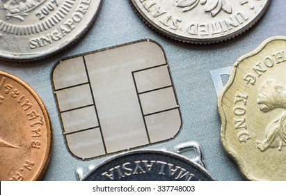 Microchip credit card and coins from different currencies close-up