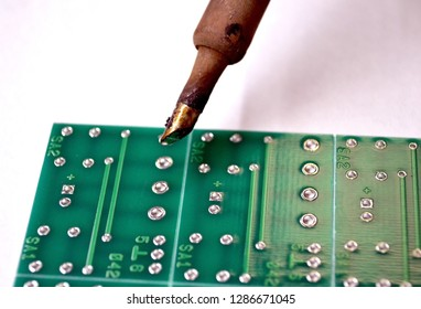 Microcircuit and soldering iron isolated on white background