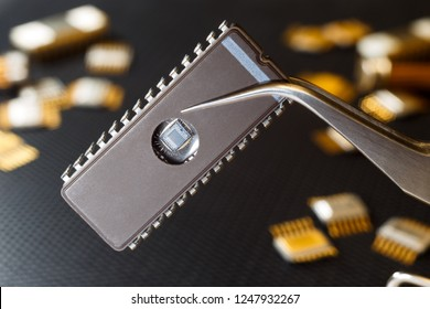 Microcircuit with tweezers on the background of electronic components.