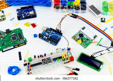 Microcontrollers, chips, resistors and light-emitting diodes on white desktop of hardware engineer