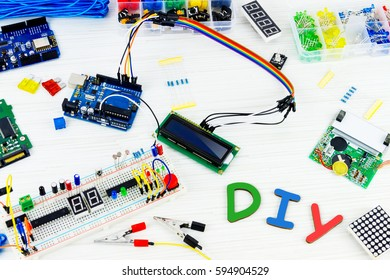 Microcontrollers, chips, resistors and light-emitting diodes on white desktop of hardware engineer. Do it yourself concept