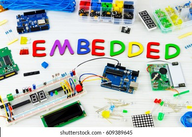"Microcontrollers, chips, resistors and light-emitting diodes on white desktop of hardware engineer. Colorful letters connected together to word ""embedded"""