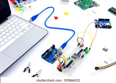 Microcontrollers, chips, resistors, usb cables and notebook on white desktop of hardware engineer. Engineer workplace