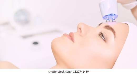 Microcurrent light esthetics procedure. Beauty girl face. Cosmetology machine. Doctor hands. Two micro balls. Wrinkle reduction.