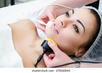 Microcurrent therapy. Beautiful young girl on the procedures for skin care. Hardware cosmetology. Cleaning of the face skin in the spa