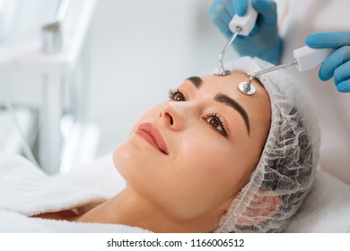 Microcurrent therapy. Pleasant nice woman having a microcurrent therapy while visiting a beauty salon