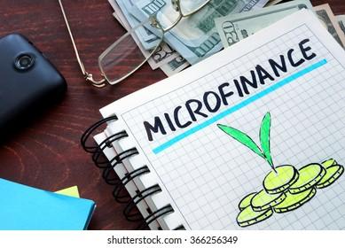 Microfinance written on a notebook. Business concept.