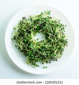 microgreen mustard sprouts on a white plate on a light background. Raw sprouts, microgreens, healthy eating concept
